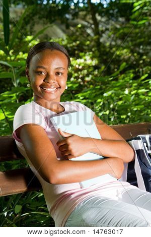 african american student sitting on bench