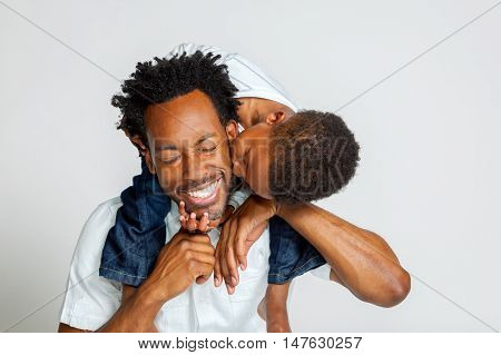 An African American boy on the shoulders of his father leans over to kiss him on the cheek. His father laughs with closed eyes.