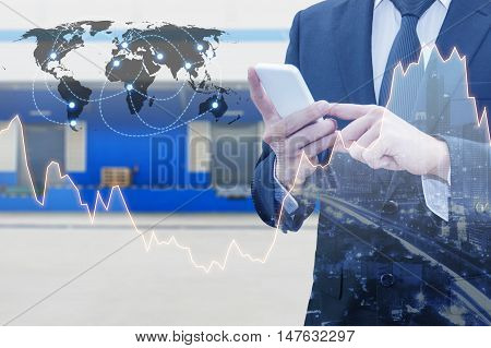 Double exposure of businessman connect internet smart phone and distribution logistic warehouse with world financial graph Business finance trading and banking concept element of this image furnished by NASA