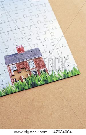 Jigsaw puzzle of a house with a piece missing