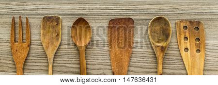 Kitchen wooden utensil of scapula, spoon and fork on wooden table