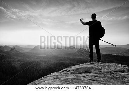 Strong man hiker taking photo with smart phone at mountain peak. Marvelous daybreak. Black and white photo