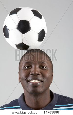 Smiling man bouncing soccer ball off head