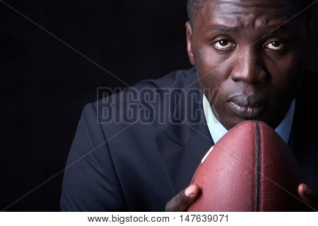 Serious businessman with rugby ball looking at camera