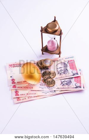 hourglass with Golden egg and indian money or indian currency over white background. Shallow focus.