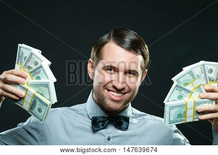 Excited young man holding cash money