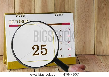 Magnifying glass in hand on calendar you can look Twenty Five date of monthFocus number Twenty Five in OctoberConcept in business and meetings.