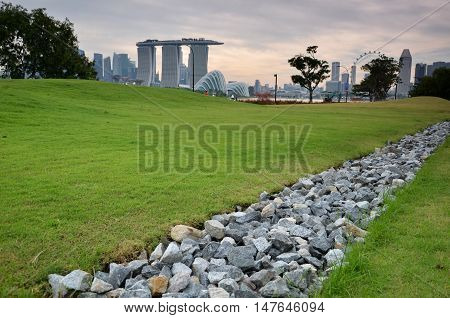 Stone and green grass in the garden with Singapore Skyline