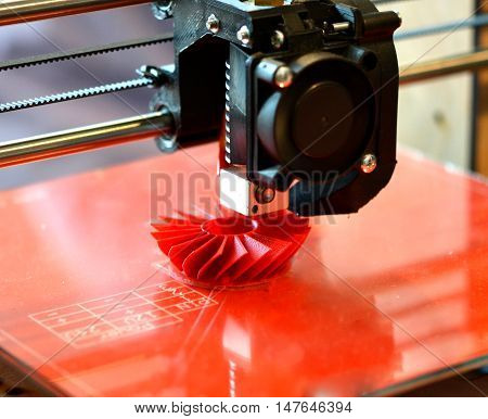 3D printer prints red shapes on a red background