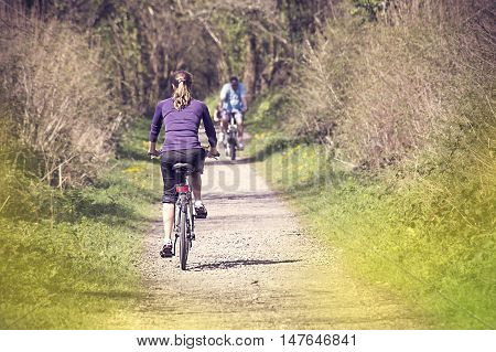 Young woman bicycling in the forest in the early spring