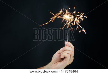 christmas, holidays, new year party and pyrotechnics concept - male hand holding sparkler or bengal light burning over black background