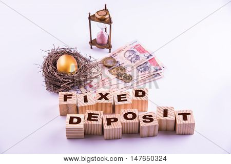 indian currency notes with coins and golden egg along with antique sand clock and wooden blocks with FIXED DEPOSIT alphabates written over it