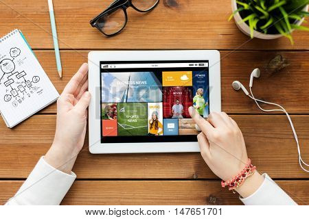 business, education, technology, people and mass media concept - close up of woman with internet news application on tablet pc computer screen on wooden table