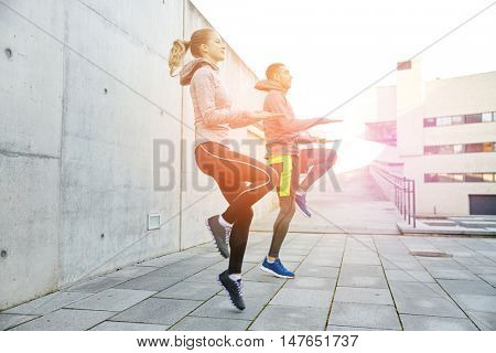 fitness, sport, people, exercising and lifestyle concept - happy man and woman jumping outdoors