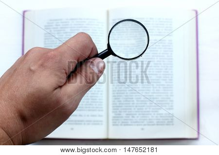 hand with magnifying glass on the background of an open book / thorough examination of information