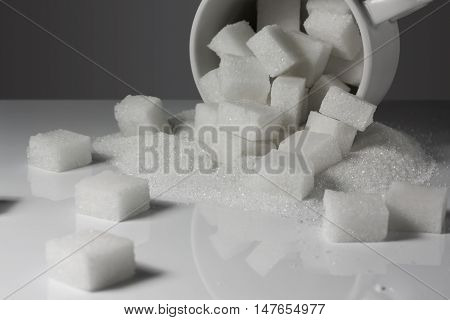 Pieces of lump sugar in a cup on a black and white background gradient.