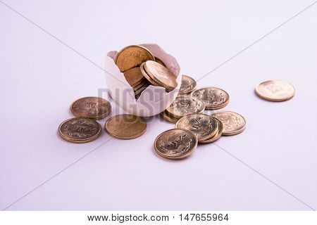 indian five rupee coins emerging from cracked egg, indian rupees and cracked egg, selective focus, isolated over white background