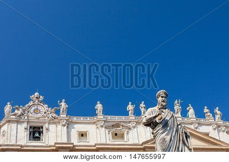 Statue of Saint Peter St. Peter's Basilica and statues standing on the roof of St. Peter's Basilica on the background Vatican. Italy