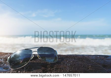 glasses on a log with white sand beach and blue sky background Travel relax vacation