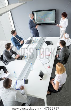 Workers group at meeting table listen managerâ??s future plan while his female assistant write notes