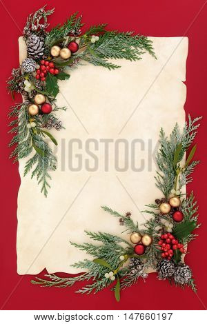 Christmas abstract background border with gold and red bauble decorations, holly, mistletoe, snow covered cedar cypress and pine cones on old parchment paper over red.