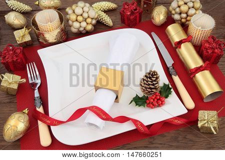 Luxury christmas dinner table setting with white plate, linen serviette, holly, gold bauble decorations, candles, ribbon and cracker on red place mat over oak background.