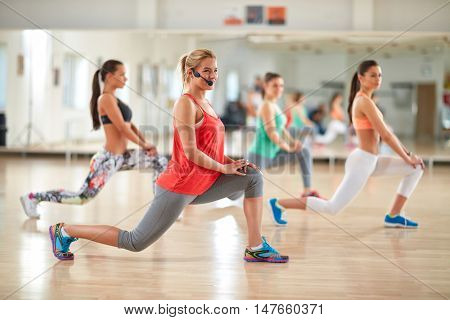 Young female aerobic instructor with headset train in fitness center