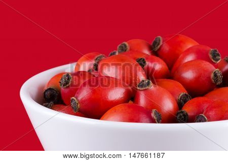 Rose hips in white bowl on red, also rose haw or rose hep. Ripe red fruits of roses, used for herbal teas, jam and they can be eaten raw. One of the richest vitamin C sources available in plants.