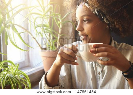 Young Fashionable Dark-skinned Woman Holding Cup Of Hot Drink, Enjoying Coffee Or Tea, Trying To War
