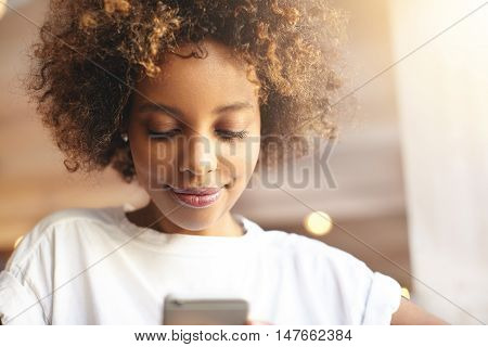 Portrait Of Good-looking African Woman In White Top Browsing Internet, Updating Applications, Using