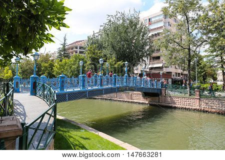 ESKISEHIR TURKEY - SEPTEMBER 03 2016: People passing over the bridge on Porsuk River. Porsuk river is one of the most populer touristy place with boat tours and entertainment in Eskisehir.