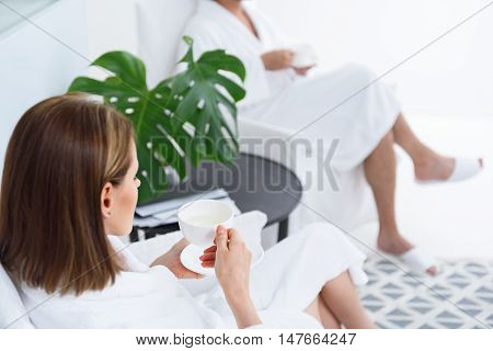 This is exactly what I needed. Rear view of woman holding cup with hot drink while enjoying weekend in spa with man wearing robe in background