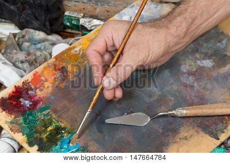 male hand with a brush mixes the paint