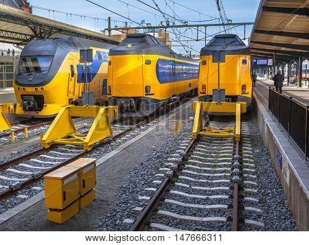 Three Fast Modern Passenger Commuter Transport Trains Waiting At A Station