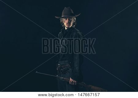 Retro 1900 Western Cowboy Standing With Rifle. Young Man. Studio Shot.