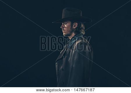 Side View Of Vintage 1900 Cowboy. Young Man. Studio Shot Against Dark Wall.