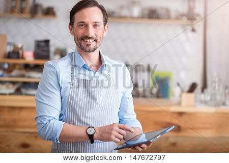 Own business. Smiling and positive man using digital tablet while standing in his own cafe