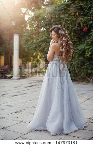 Young beautiful bride in a long white wedding dress,a brunette with long curly luscious hair in the hair stabbed the big beautiful hair,pretty smile,posing standing up in sex trafficking to the photographer in the lush green Park outdoors in the summer