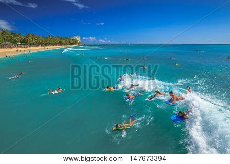 Waikiki Oahu Hawaii - August 27 2016: Boogie boarding bodyboarding also called is a popular water sport practiced in Waikiki Beach near the Waikiki Pier at Queens Surf Beach in Honolulu.