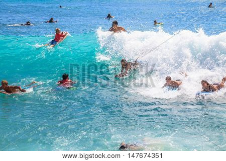 Waikiki Oahu Hawaii - August 27 2016: children and teens have fun with the most popular watersport Waikiki Beach in Honolulu: the boogie boarding or bodyboarding.