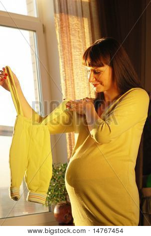 Pregnant woman waiting for a first child. Sunlight from window.