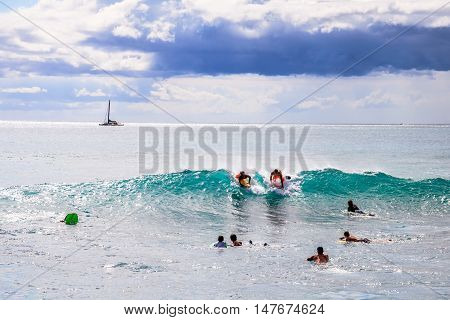 Waikiki Oahu Hawaii - August 27 2016: people on vacation having fun swimming on boogie board at Queens Surf Beach a section of Waikiki Beach in Honolulu.