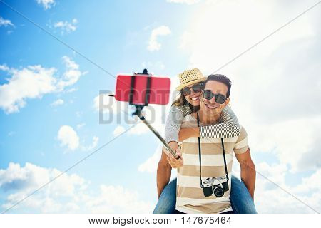 Happy young couple on summer vacation having fun taking a selfie on a stick with the young woman riding piggy back on the mans shoulders as they stand against a cloudy blue sky grinning at the camera