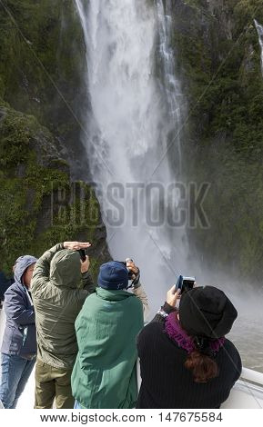 Milford Sound, New Zealand - February 2016: Tourists On The Cruising Boat Approaching Stirling Falls