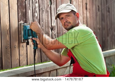 Worker polishing old wooden fence with power tool - a vibrating sander scraping the cracked paint