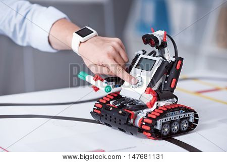 Experiment. Male finger pressing button on small robot in order to make machine to use green marker