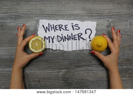 Where is my dinner? Half a lemon in the left hand and whole lemon in the right hand on the gray wooden textural background