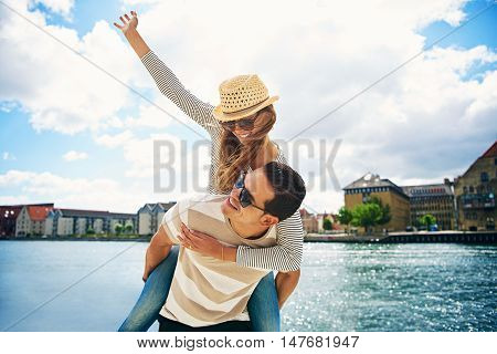 Fun loving young couple frolicking at the waterfront of a historic town riding piggy back and laughing enjoying the freedom of their summer vacation