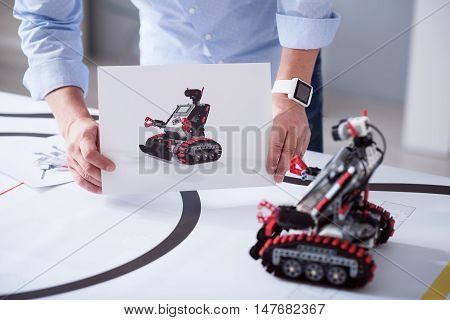 Compare. Male hands holding an image of a robot next to the real robot