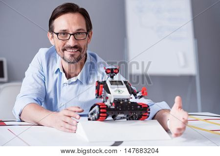 Proud and satisfied. Portrait of a man in glasses smiling while demonstrating new technologies